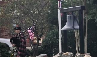 Man playing bagpipes in front of large bell